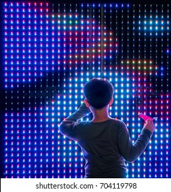 Asian boy playing with colorful led light interaction wall