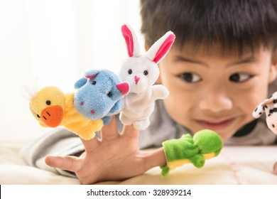 Asian boy playing with finger puppets ,focus on rabbit