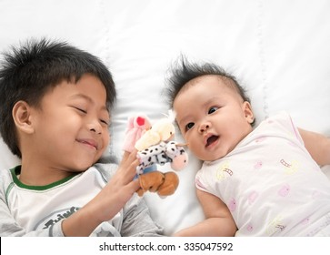 Asian boy playing  finger puppets for his sister on black and white background, asian family
