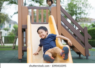 An Asian boy is playing in playground with happy face