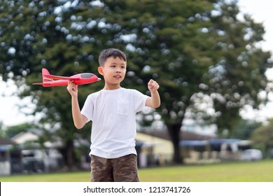 Asian boy playing red colour toy glider at playground.