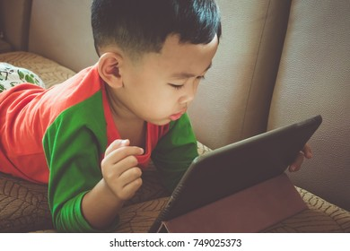 Asian boy is playing the tablet in the room.