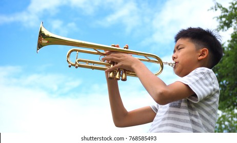Asian boy playing trumpet with blue sky background.