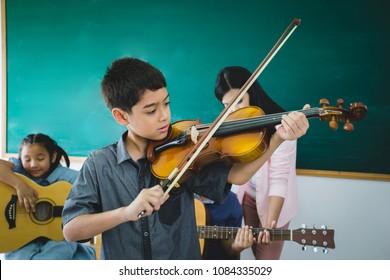 Asian boy playing violin in music school