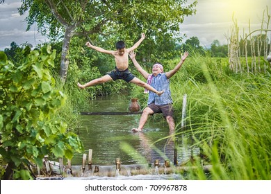 Asian boy playing water in rice field with father