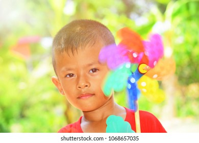 The Asian boy is playing wind turbine for relaxing in outdoor with fun, concept for family happiness.