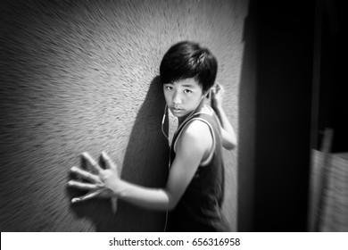 Asian boy posing against wall