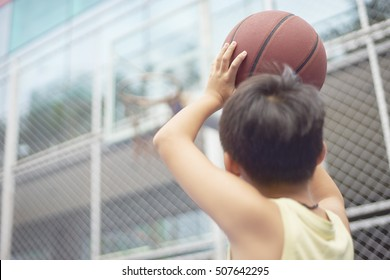 Asian boy preparing for basketball shooting at playground