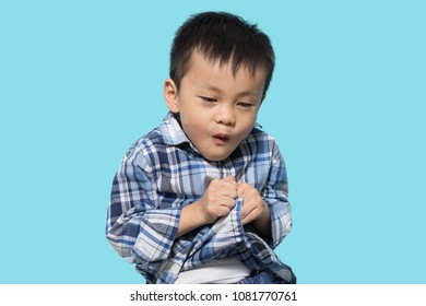 Asian boy pretend to be scared and acts like afraid but makes funny face, blue background
