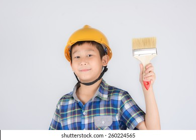 Asian boy in a protective helmet with brush in his hand
