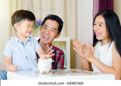 Asian boy putting coins into piggy bank, junior saving account conceot