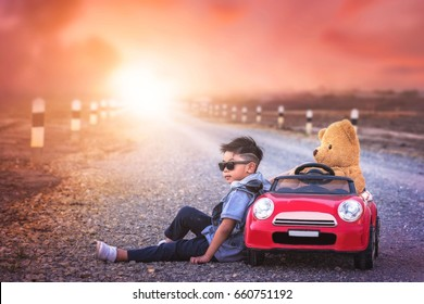 asian boy relaxation with teddy bear on big toy car.My son sit on road happy day