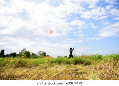 Asian boy running and playing on the grass field on blue sky background.Happy little children flying kite.