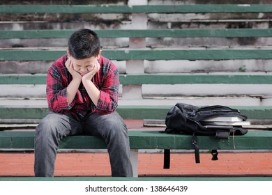 asian boy sitting on a concrete bench shows unhappy expression