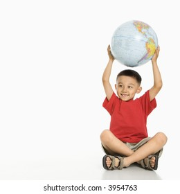 Asian boy sitting on floor holding Earth globe over his head.