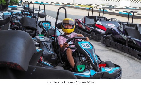 Asian boy sitting on go kart ready for a race.