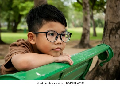 Asian boy sitting on the green bench, in the park, thinking about girlfriend. Kid model acting for take a photo, relax day in the garden, peaceful, dream to future.