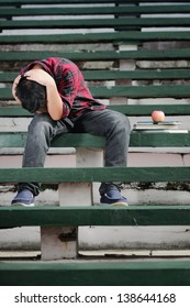an asian boy sitting on a green concrete bench with hands on his head and shows frustrated expression