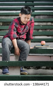 an asian boy sitting on a green concrete bench with sad expression