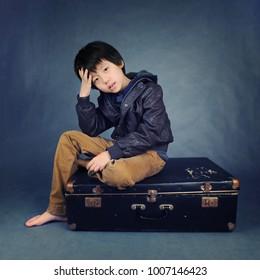 Asian boy sitting on suitcase