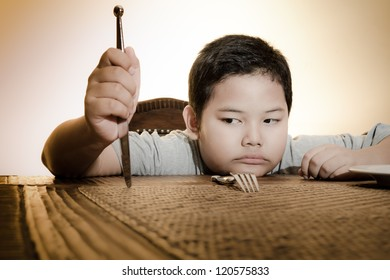 asian boy sitting sadly on dining table waiting for food