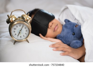asian boy sleeping on bed white pillow and sheet with alarm clock and teddy bear.boy sleeping in morning wearing sleep mask