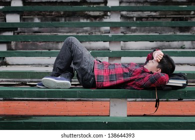 an asian boy sleeping on a concrete bench with hand over his forehead