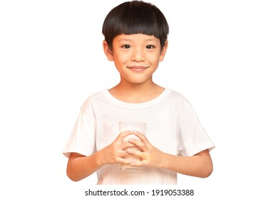 The Asian boy smile happily hands holding a glass of milk. Asian pretty boy drinking the milk isolated on white background. clipping paths