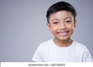 An Asian boy smiling wearing a white t-shirt on a grey background. Copyspace on left side of the kid.