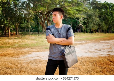 An Asian boy standing with his briefcase is studying via on line network.