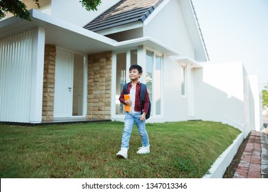 asian boy student with backpack and book standing in front of his house ready to walk to school in the morning