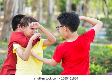 Asian boy student or children getting bullied on outdoor. School friends bullying a sad little boy in park. education, bullying, conflict, social relations and people concept
