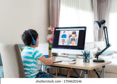 家庭のリビングルームで、教師や同級生と一緒にコンピューターを使って、アジアの少年学生のビデオ会議e – ラーニングを行う。ホームスクーリングと遠隔学習、オンライン、教育、インターネット。