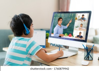 Asian boy student video conference e-learning with teacher and classmates on computer in living room at home. Homeschooling and distance learning ,online ,education and internet. - Shutterstock ID 1760879942