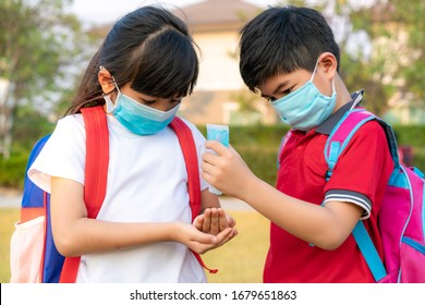 Asian boy student wear hygienic mask and press alcohol gel from bottle to hand's sister for protect  covid-19 coronavirus and epidemic virus after back from school.