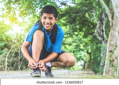 Asian boy student wearing shoes before go to school