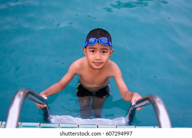 Asian boy swimming in the outdoor public pool.Portrait of swimming child with goggles after training in water pool.