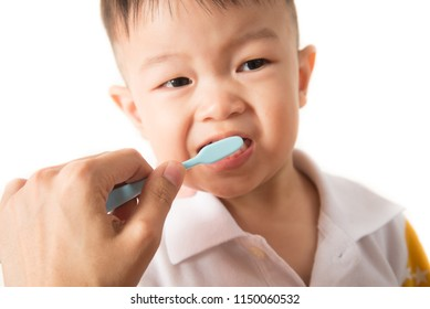 Asian boy take a  toothbrush cleaning teeth by his mother