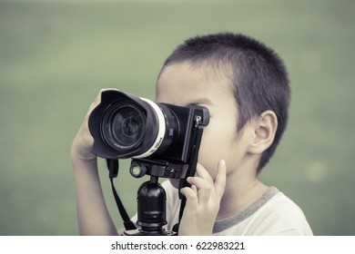 Asian boy is taking a photo in the garden with vintage color tone