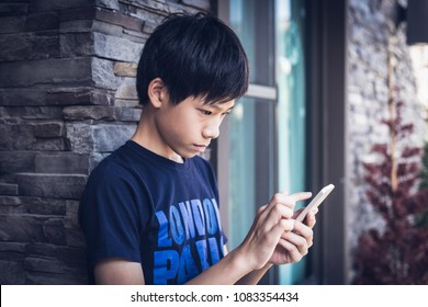 Asian boy teenager in dark blue t-shirt, serious face expression and finger point at mobile, using wireless smartphone outside the home. Daylight outdoor background with stone wall, window, house.