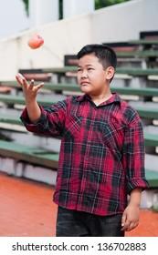 asian boy throwing an apple