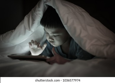 Asian boy using tablet screen while lying on bed under white blanket, in the bedroom at night, bright screen light reflex on little kid face and his finger hand pointing at  internet device.