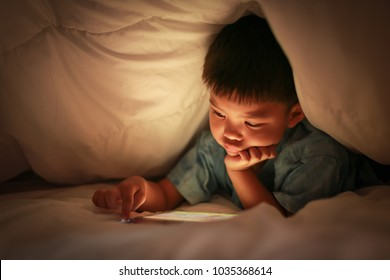 Asian boy using tablet watch online cartoon and kid contents, fingers touch on touchscreen, while lying under white blanket in the bedroom at night, bright screen yellow light reflex on his face.