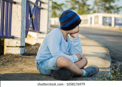Asian boy, wearing blue clothes, black-and-blue hat, sitting sad and lonely at the old bridge.