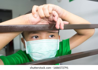 Asian boy wearing a mask waiting anxiously in front of the house window grille during corona virus outbreak.