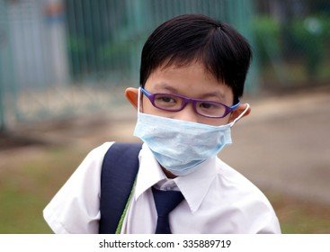 Asian boy wearing mouth mask against air pollution. Selective focus and shallow DOF