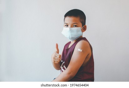 Asian boy wearing protective mask against covid-19 with showing her arm after getting vaccine.