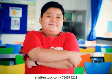 Asian boy wearing a red T-shirt smiling and standing in his school cafeteria