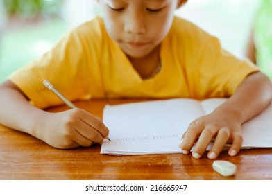 Asian Boy Writing English Alphabets.
