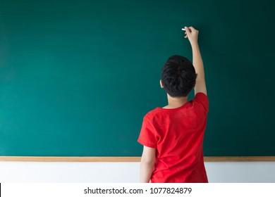 Asian boy writing on empty green board in class room at school